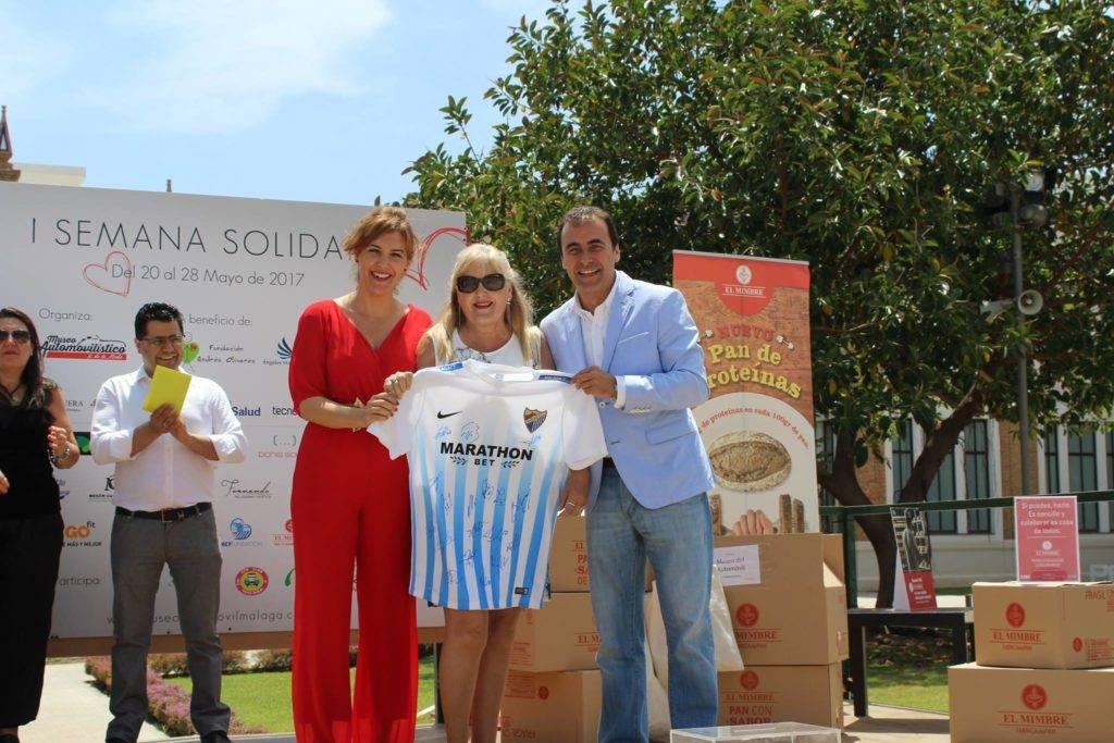 Moment de la entrega de la camiseta del Málaga Club de Fútbol firmada por todos los jugadores a la ganadora en la Subasta Solidaria