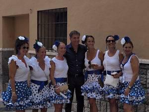 El entrenador del Málaga CF posa así de sonriente con un grupo de preciosas malagueñas ataviadas para ceebrar la Feria del Centro Histórico de Málaga